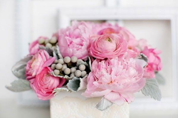 low wedding centerpiece with pink ranunculus, peonies, and dusty miller in white box vase