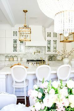 Stunning white transitional kitchen with brass chandeliers, faucets, pot filler and handles. Two-toned La Cornue stove.