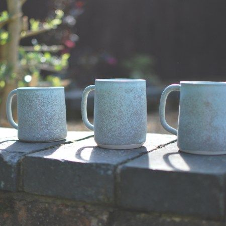 3 Speckle porcelain mugs sitting on a wall. Artist Helen Button