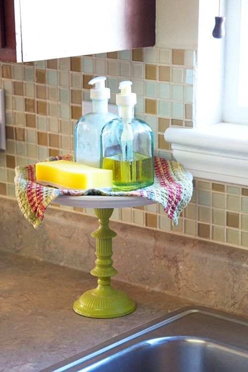 Nice way to keep kitchen soaps, etc. high, dry and neat.    Build a tray stand to hold your kitchen necessities--purchase a candle stand and a cake plate or tray from your local dollar store and hot glue them together. This will keep items dry and out of the way while working in the kitchen!