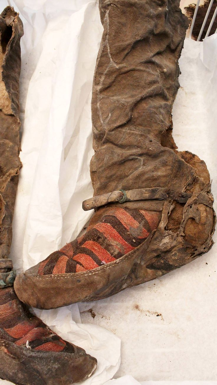 Felt boots - which feature red and black stripes and metal buckle work -  recovered from