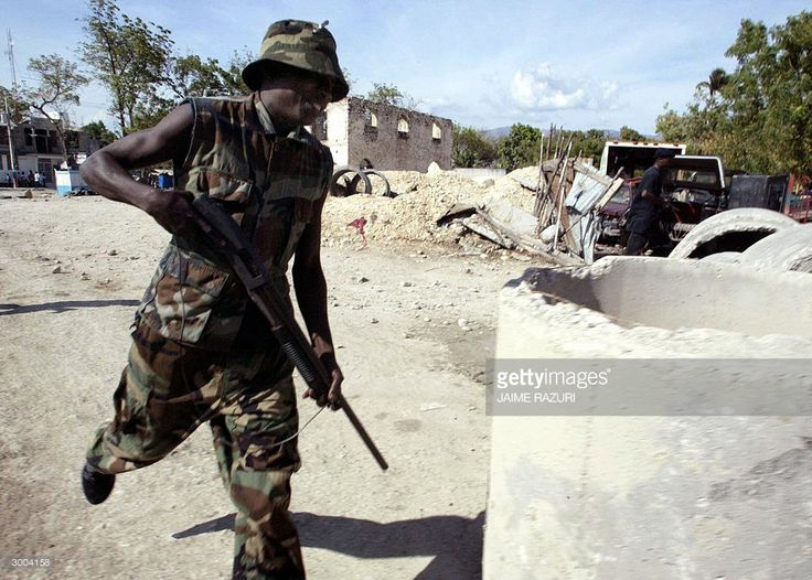 Armed supporters of Haitian President Jean Bertarnd Aristide, known as 'Choime', run close to a police station in Bon Repos, 30 kms north of Port-Au-Prince, 22 February 2004, that was attacked by susspected rebels the previous night. The crisis in Haiti exploded 22 February 2004 as armed rebels took control of the country's second largest city after seizing the airport there, complicating frantic international efforts to end a political deadlock in the capital.