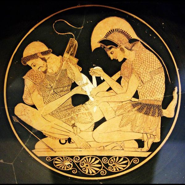 PATROKLOS AND ACHILLES The younger, beardless Achilles wraps a bandage around the arm of his older, bearded friend. Achilles is in full armor, but without shinguards. Patroklos, who looks away in pain and squats on a shield . There is no such scene in the Iliad, but the painting was inspired by the intimacy of the two men and modeled on the scene where Patroklos binds the wounds of Eurypylos. Athenian red-figure wine-cup (kylix) by Sosias found in Vulci, Italy, c. 500 bc.