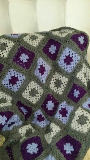 Crocheted granny square blanket made in purple and  grey.