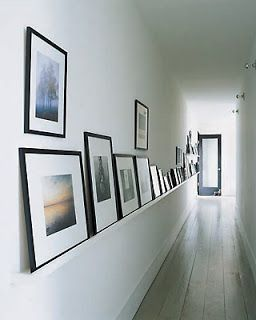 A picture ledge holds a selection of clasically framed photographs in the hallway of Peri Wolfman and Charles Gold's home.