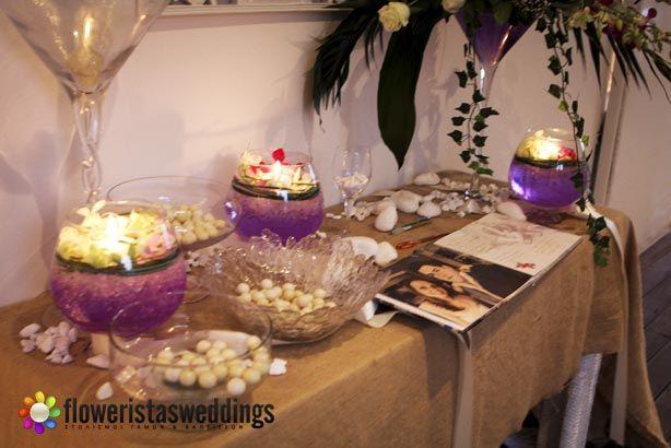 Τραπέζι ευχών γάμου με γλυκίσματα ,φρέσκες ορχιδέες σε συνθέσεις με jel και κεριά και το καθιερωμένο βιβλίο ευχών.