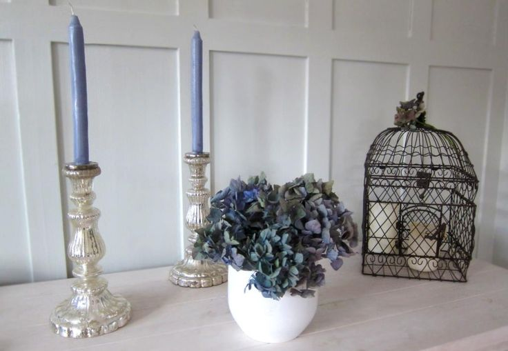 autumn decoration: air dried blue hydrangea with birds cage and silver candleholders