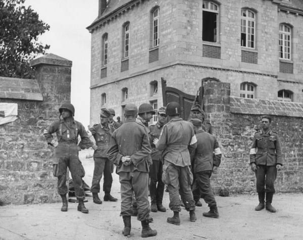 American Red Cross and German Red Cross workers in army uniforms mingling and talking at gates of courtyard as they wait to take care of wounded of both armies. Ste Mere-Eglise, June 7, 1944