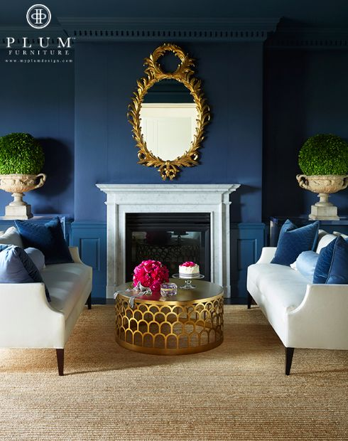 Love the cocktail table & the navy/gold combo. #navy walls #gold cocktail table #gold coffee table #living room #gold fireplace mirror #fireplace mirror