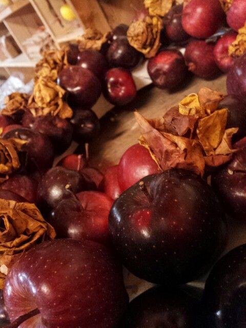 Ghirlanda di mele piccole e rose fatte con le foglie