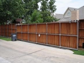 Cedar sliding fence crosses the driveway making the outdoor area larger and more private. By Outdoor Signature in Argyle, TX