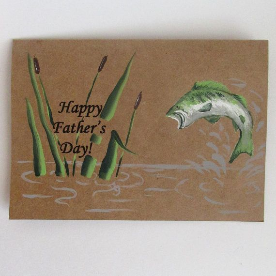 This is a hand-painted Fathers Day card for the fisherman in your life. The card features a hand-painted large mouth bass jumping out of the water amongst the cattails. The message, Happy Fathers Day is printed on the outside of the card. The inside of the card is blank so that