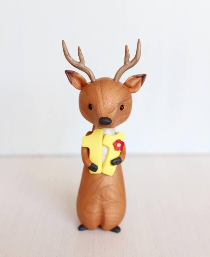Forme de gâteau d'anniversaire cerf est sculpté en pâte polymère avec ajouté poudre minérale de Mica pour une subtile brillance et effet marbre élégant. Elle est titulaire d'un numéro et est décorée avec des fleurs. Fabrication artisanale à la commande, votre figurine de chevreuil