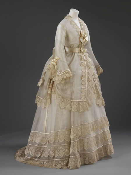 Wedding dress, silk gauze and lace bodice and skirt, satin sash, collar, cape and silk fragment which was probably made in Great Britain or France, c. 1872-1874. Find out more http://collections.vam.ac.uk/item/O249340/wedding-dress-unknown/