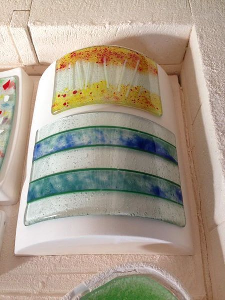 Two fused glass pieces. The green and blue was created working with glass enamels, left to dry then cut alongside plain glass with stringers between each top slice. The top autumn piece was created using white stringers and glass frit pounded until I liked the sizes of pieces.