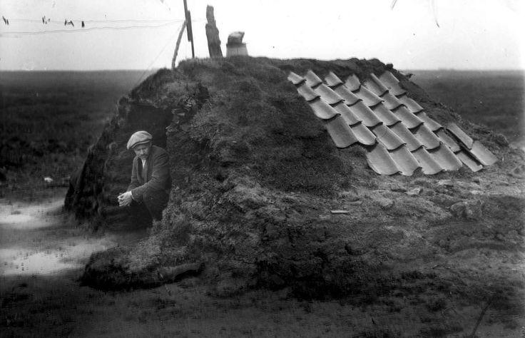 Krotten, achterbuurten, sanering: Een man zit in Drenthe in zijn plaggenhut, bedekt met een aantal dakpannen. Nederland, 1936.