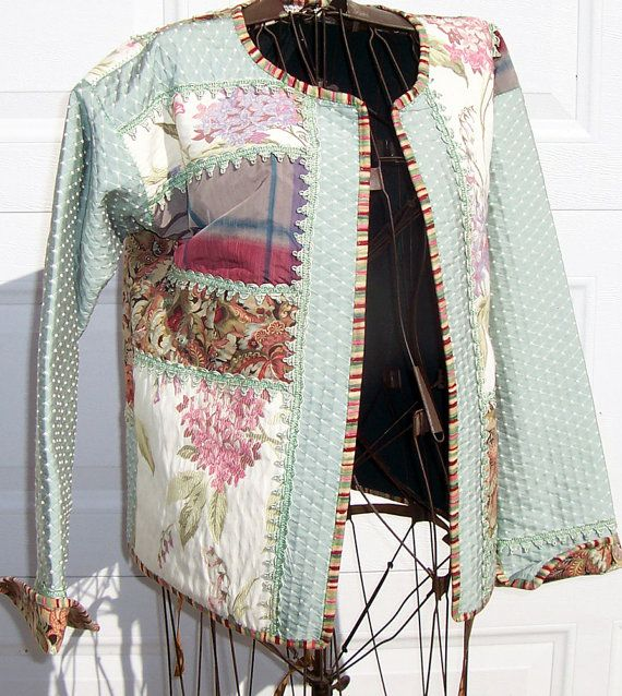 This womens size large quilted sweatshirt jacket features blocks of silk, tapestry and cotton fabrics in celedon greens, rusts, deep pinks and a touch of lavender. Each block of fabric is bordered with a beautiful vintage celedon green braid. The sleeves have a cuff that can be worn up to show the cotton print or down to show the celedon green tapesty fabric and vintage braid. The inside of the jacket is the soft dark green fleece of the sweatshirt. All of the fabrics have been pre-washed so…