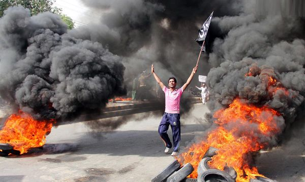 LAHORE: May15 – Man walks past burning tyres during a demonstration by traders of Akbari Mandi against prolong electricity loadshedding in the area.