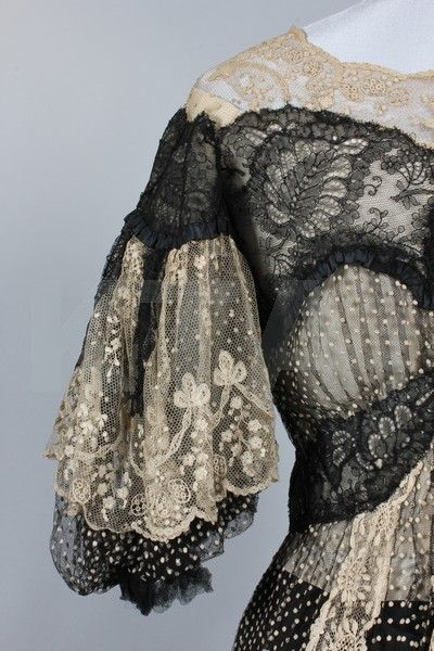 A black and ivory point d'esprit summer dinner gown, circa 1902, the gros grain waistband woven 'Raudnitz & Co, Huet & Cheruit Frs, 21 Place Vendome, Paris',