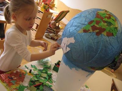 ballon met krantenpapier, blauw verven, er sjablonen op tekenen voor de werelddelen en die beplakken met bruin en groen gekleurd papier