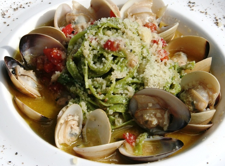 Spinach linguine tossed with white shell clams baby vegetables and anchovy butter