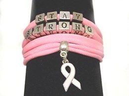 De armband is gemaakt van elastisch ibiza lint met daarop geregen metalen letterkralen en een pink ribbon bedel. Doordat de armband elastisch is past het altijd.