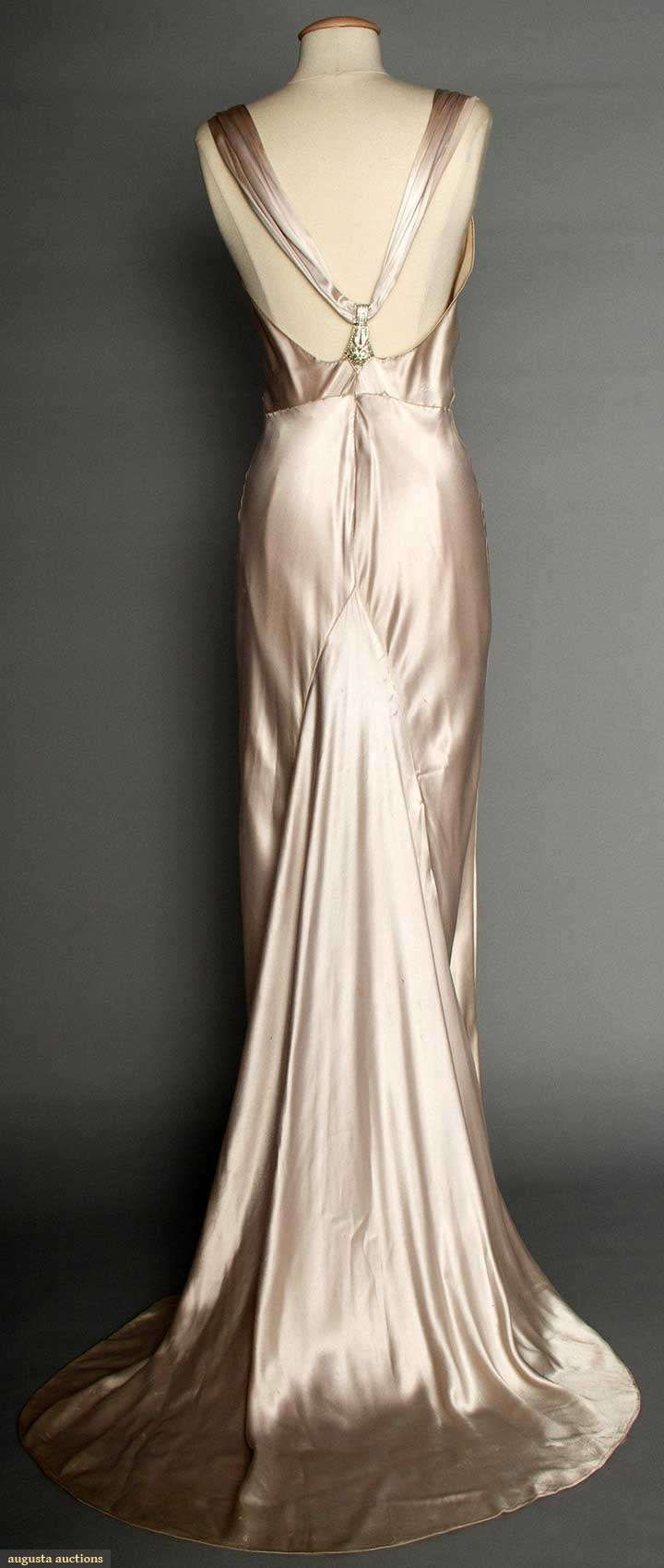 "SILVER SATIN EVENING GOWN, 1930s Pale lavender/silver silk charmeuse, bias-cut, sleeveless, cowl neckline, open back, jeweled Deco elements on shoulder straps & at CB, floating trained back panel, labeled ""NRA Code, Made Under Dress Code Authority PHB038577""  