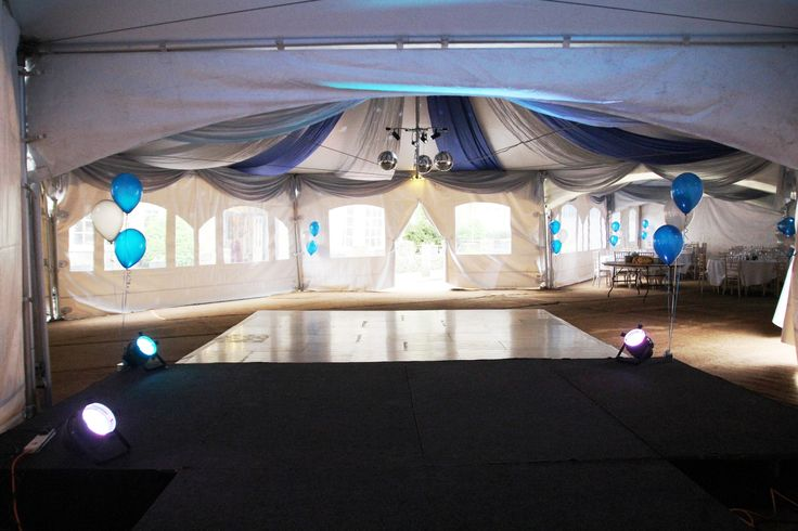 Fairford Town Ball marquees with blue and silver drapes and swags. This is looking through the tents from the stage.