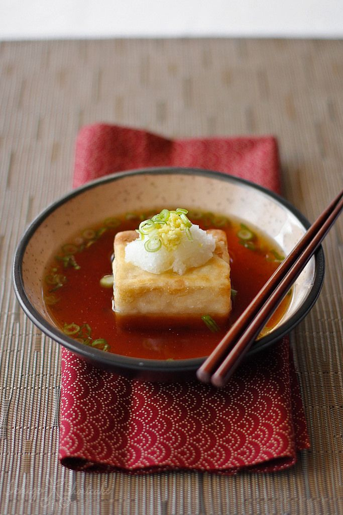 Agedashi Tofu (揚げ出し豆腐): A Japanese starter with crispy fried tofu in a light soy-based sauce seasoned with daikon radish and ginger.