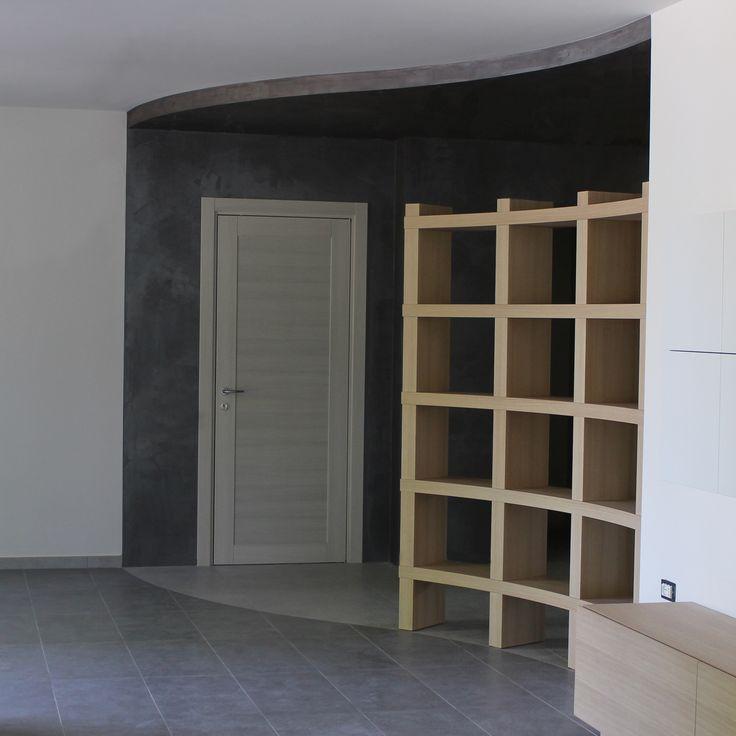 Progetto d'arredo per abitazione privata. La libreria curva in legno, segue la curva del pavimento bicolore. Ristrutturazione d'interni a cura di Trova&Rinnova.