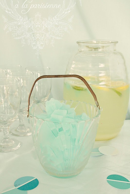 aqua star limeade ice cubes sit in a vintage seashell patterned glass ice bucket