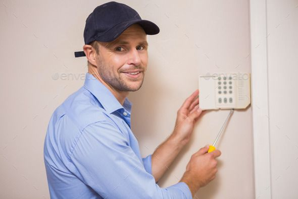 Handyman fixing an alarm system on the wall. http://photodune.net/item/handyman-fixing-an-alarm-system-on-the-wall/9621268