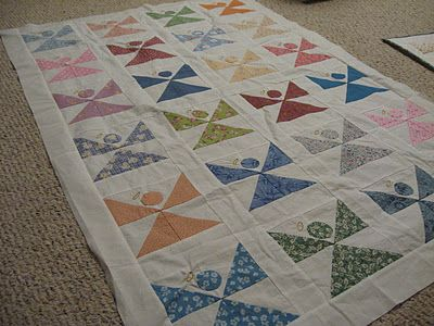 Angel quilt - These are simple blocks. Each block consists of 4 half square triangles - two arranged for the wings and two for the skirt. A circle appliqued for the head and then embroider or use cording for the halo.
