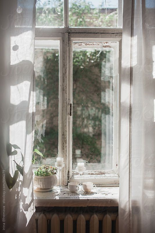 Two cups of tea on a window lighted by bright morning sun