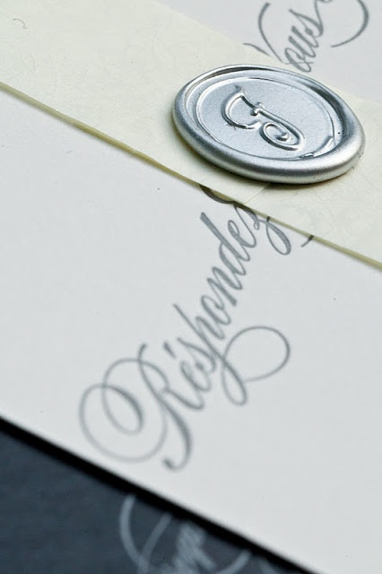 Invitations with white/silver bellyband and silver wax seal.