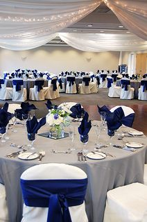 Royal blue napkins and sashes against white chair covers and gray linen. Plus, ceiling draping with twinkle lights. FestivitiesMN.com