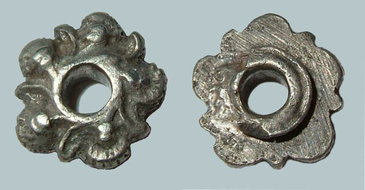 Record ID: LVPL-1D1E07 Object type: EYELET Broad period: MEDIEVAL County: Central Bedfordshire  Silver eyelet of probable Late to Post-Medieval date, c.1350-1700. The eyelet is a flower in shape with central perforation. In between each of the petals and pellets sits a curved diagonal spoke which radiates from the centre. The central perforation is raised higher than the surround. The reverse shows a raised double ridge around the perforation for attachment.