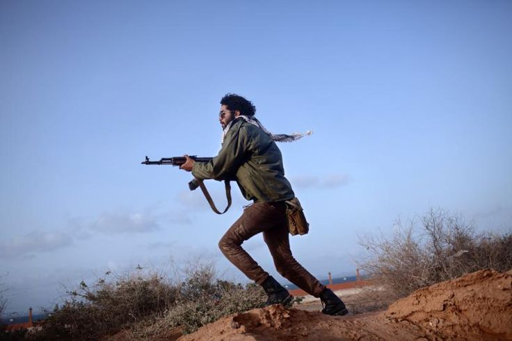 An Anti-Qaddafi rebel, armed with Kalashnikov assault rifle, clears an area near the front line in Bin Jawad in 2011.