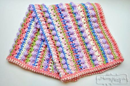 The Candy Crush Baby Blanket uses a variety of crochet stitches to create a unique texture that is fun and playful. Practice your bobble stitch, cluster v-stitch, pucker stitch, mesh stitch and more with this one-of-a-kind crochet baby blanket pattern.