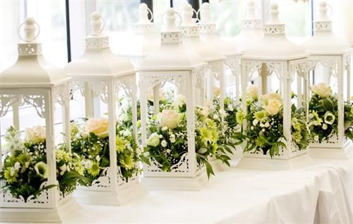 White lanterns with a touch of floral olive and bottle green to complete a simple Greek touch to your wedding