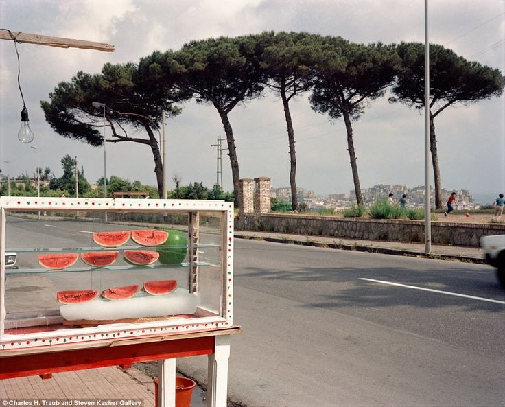 A watermelon stand on the roadside in Milan tempts passing cars. Meanwhile, a group of children play football in the background