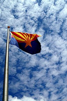 The flag of the state of Arizona_consists of 13 rays of red & weld-yellow on the top half, the colors of the flag of Spain, representing the 13 original states. The red & yellow also symbolize Arizona's picturesque sunsets. The copper star represents the copper mining industry in Arizona. The rest of the flag is colored blue, representing liberty.  Officially, the State of Arizona website, museum and official materials cite the following origins of the Arizona flag: