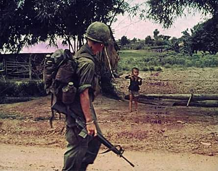 """A member of """"B"""" Company, 1st Battalion, 27th Infantry Regt. (Wolfhounds) 25th Infantry Div, waves to a small Vietnamese boy as the company passes a village during a search and clear operation near Fire Support Base """"Kien"""" August 21,1970."""