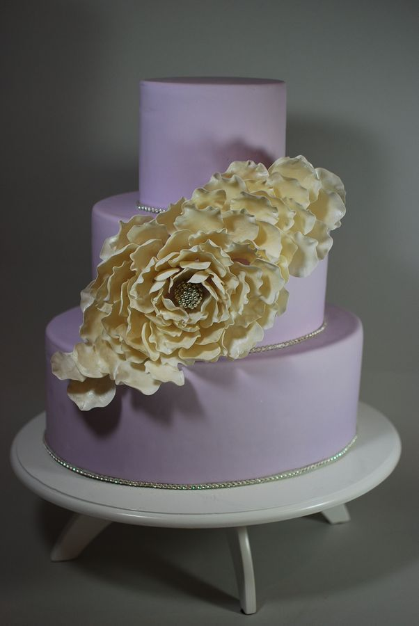 This lavender oval tiered cake had rhinestone borders and one big flower.  I made the center of the flower by using so sticky sap on a gumpaste ball.  I know some people put their petals directly on the cake, but I wanted more dimension.  I put a small piece of wire (30 gauge/white) in each petal.  I used a ball tool to thin and ruffle the petals.  A layer  of luster dust was painted on the petals.