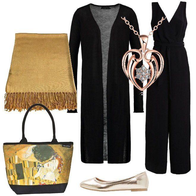 """La borsa con l'immagine del quadro di Klimt """"Il bacio"""" è l'elemento decisamente originale della composizione. Qui viene proposta con una jumpsuit nera e un cardigan lungo, da indossare con delle ballerine e un foulard dorati. Una collana con un ciondolo a forma di cuore donerà un tocco di luce."""