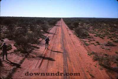 A long straight dirt road through central Australia.
