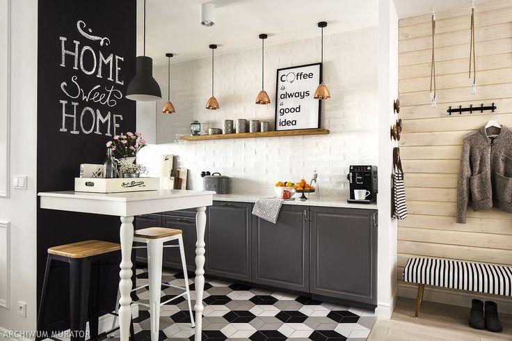 Szara kuchnia w stylu skandynawskim: pod ścianką pomalowaną farbą tablicową ustawiony został wykonany na zamówienie stolik barowy (stół barowy na zamówienie, stoltech.pl). To granica między kuchnią a salonem, miejsce spotkań przy kawie, przekąsce. Meble z frontami Bodbyn, IKEA. Kuchnia została włączona do przestrzeni przedpokoju.