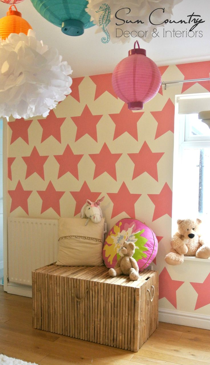 """Mermaid Cottage"" a sweet girls room makeover for two sisters! On the rear wall we designed a star template and painted pale bubblegum pink stars. We added a bamboo dress-up chest and lots of hanging lanterns & tissue paper pom poms"