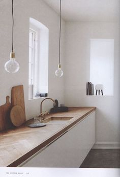 White walls can seem stark, but not when they're softened with the beautiful tones that a wooden work surface has to offer AND the right lighting