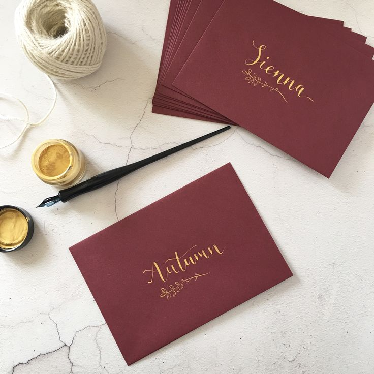Gold calligraphy names and botanical detail on burgundy envelopes for a luxury bohemian bridal shower invitation design. How gorgeous is the brides name 'Autumn' in this deep Autumnal shade too?!